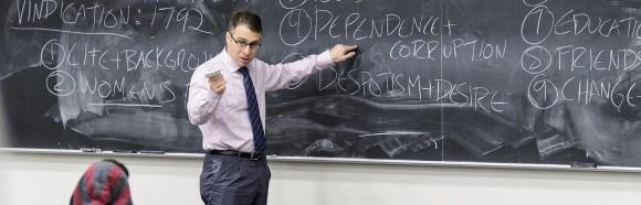 Professor gestures at chalk board.